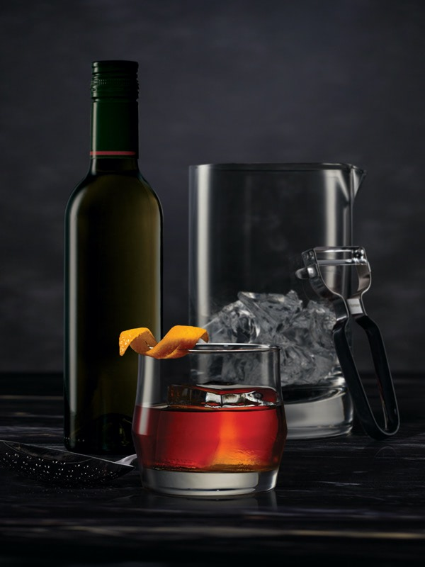 Cocktail mixing tools surrounding a Boulevardier on a dark surface