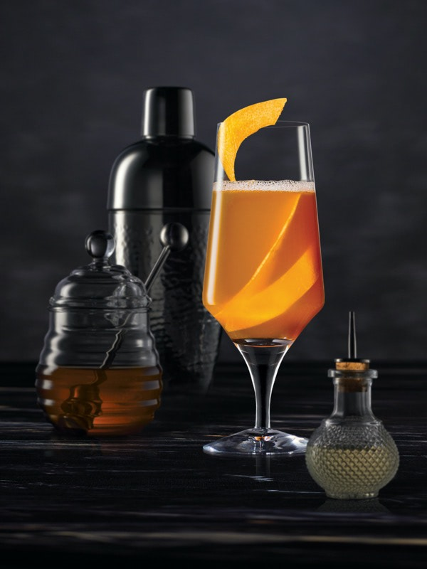 Cocktail mixing tools surrounding a Brown Derby on a dark surface