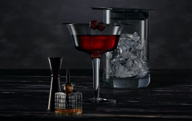 Cocktail mixing tools surrounding a Midnight Manhattan on a dark surface